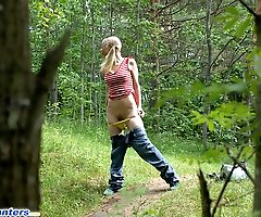 Young cute blondie waters the grass with her piss