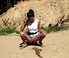 Watch brunette's river of piss flow through sand