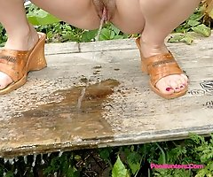 Dirty teen slut sits for a piss on a picnic table