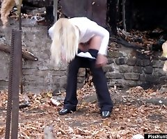 Sexy blondie relieves herself behind a building